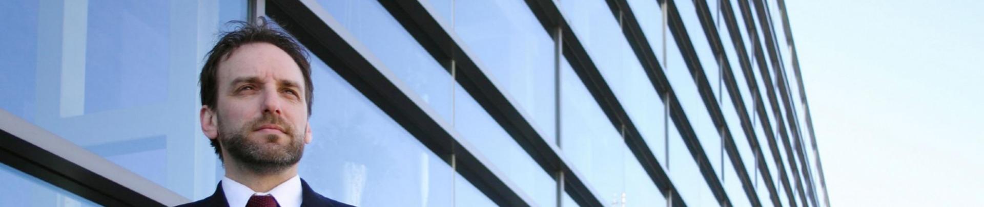 Man met snor en baard in pak staat voor glazen kantoorpand